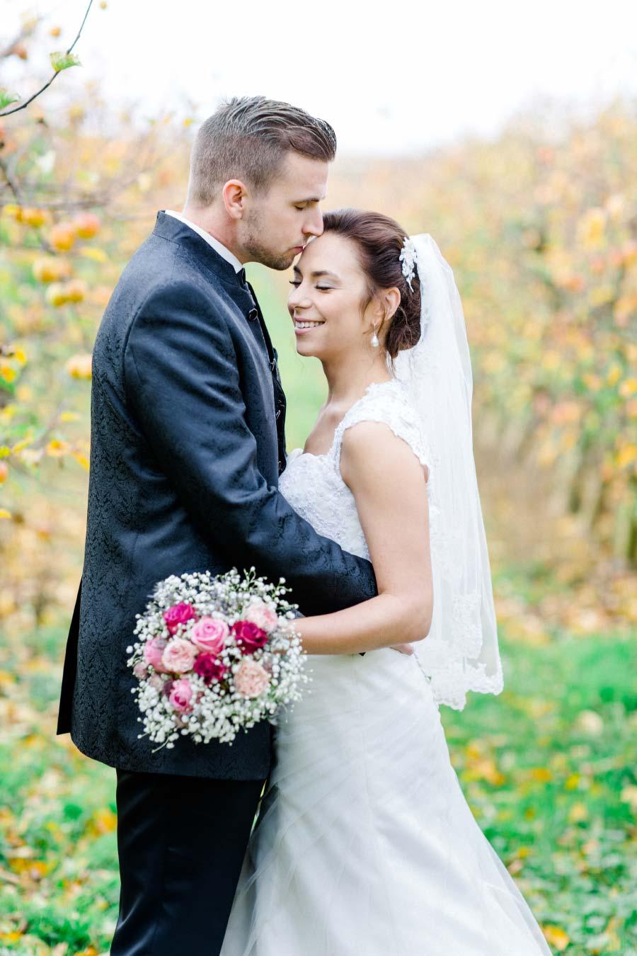 Bräutigam küsst Braut auf die Stirn