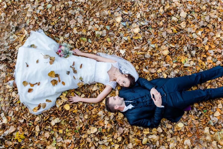 Brautpaar liegt im Blätterhaufen