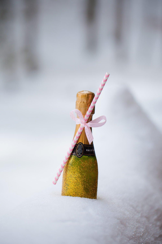Winterliche Hochzeitsinspirationen: Mit Gold Glitzer verzierte Sektflaschen mit Strohhalm für die Hochzeit