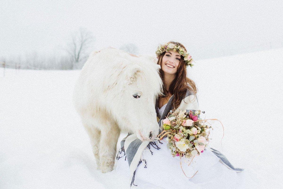 Ein Brautfotoshooting im Schnee mit Pferden