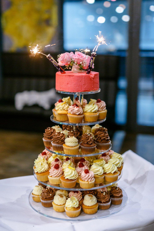Hochzeitstorte mit Cupcakes in einer kleiner Torte oben drauf