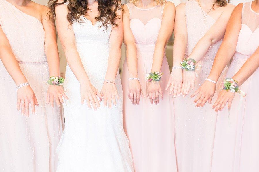 Braut mit Brautjungfern die ihre Blumenarmbänder zeigen