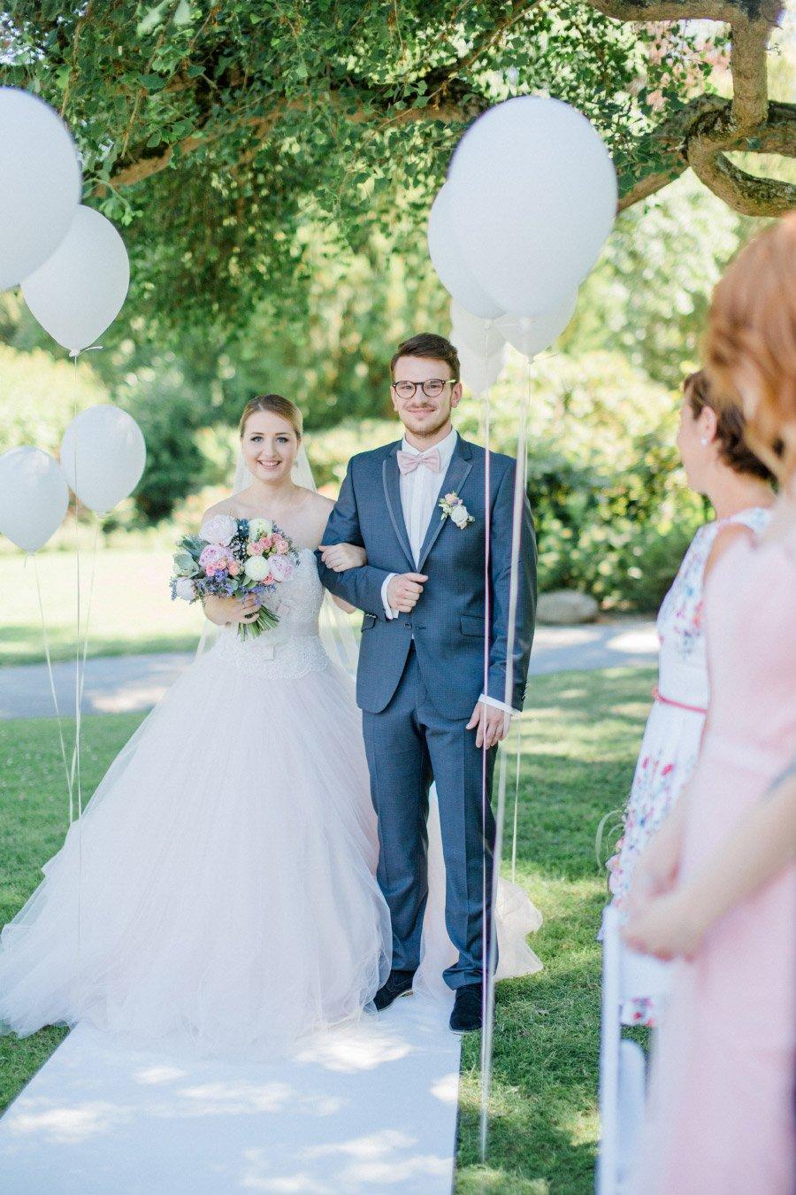 Braut und Bräutigam auf dem Weg zum Traubogen