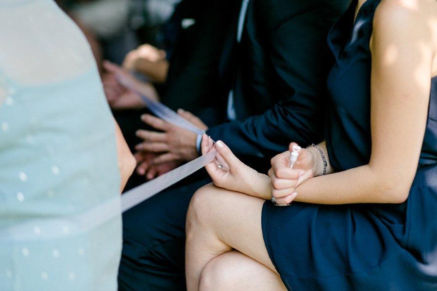 Die Ringe von Braut und Bräutigam an einem langen Band nach vorne reichen
