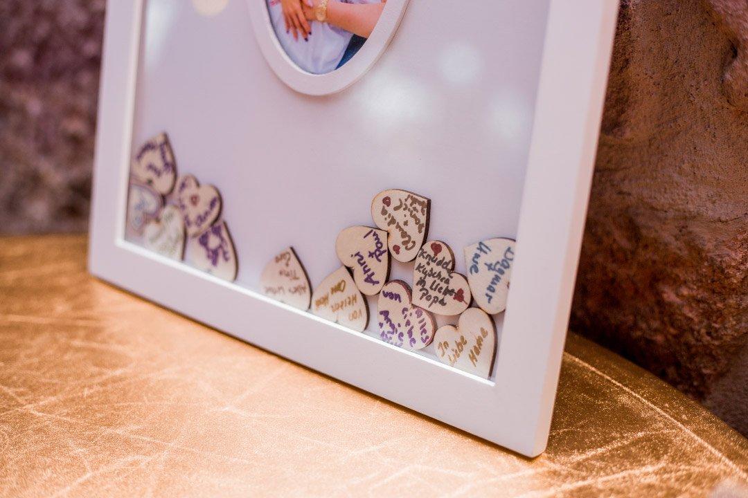 Alternatives Gästebuch mit kleinen Holzherzen im Bilderrahmen