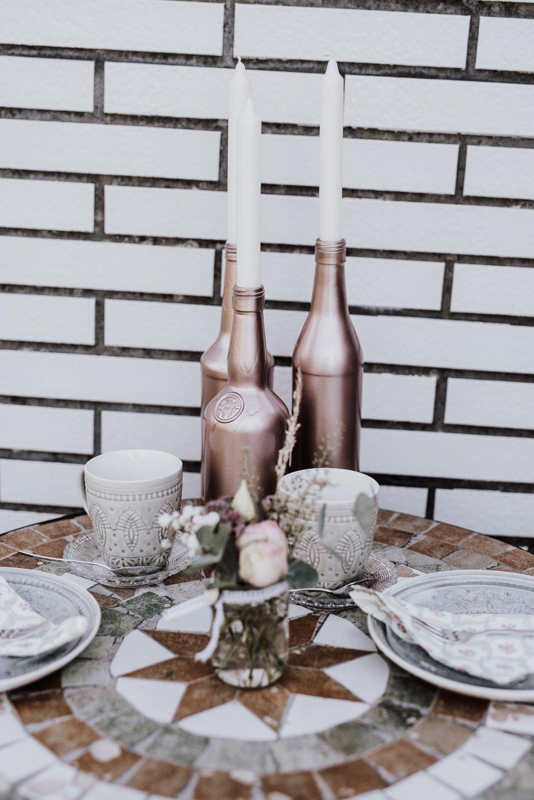 Besprühte Flaschen für die Tischdeko bei der Hochzeit