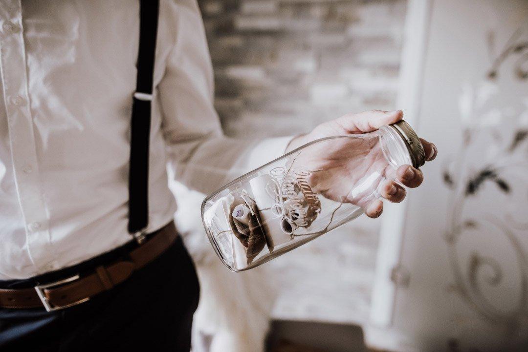 Bräutigam hält Wunschglas in Händen