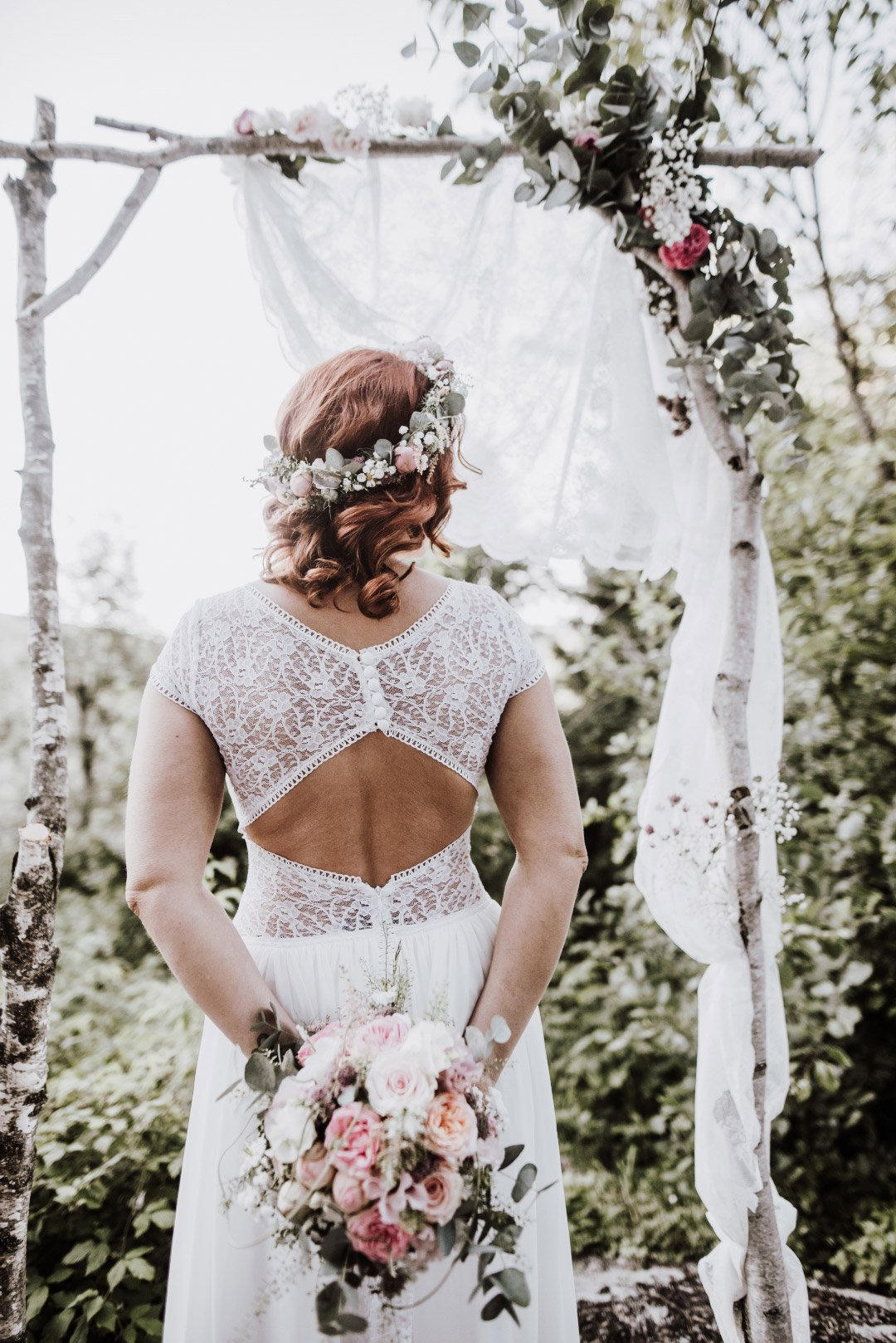Braut im Brautkleid am Traubogen