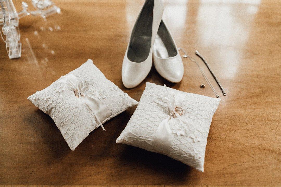 Weiße Ringkissten und Schuhe der Braut