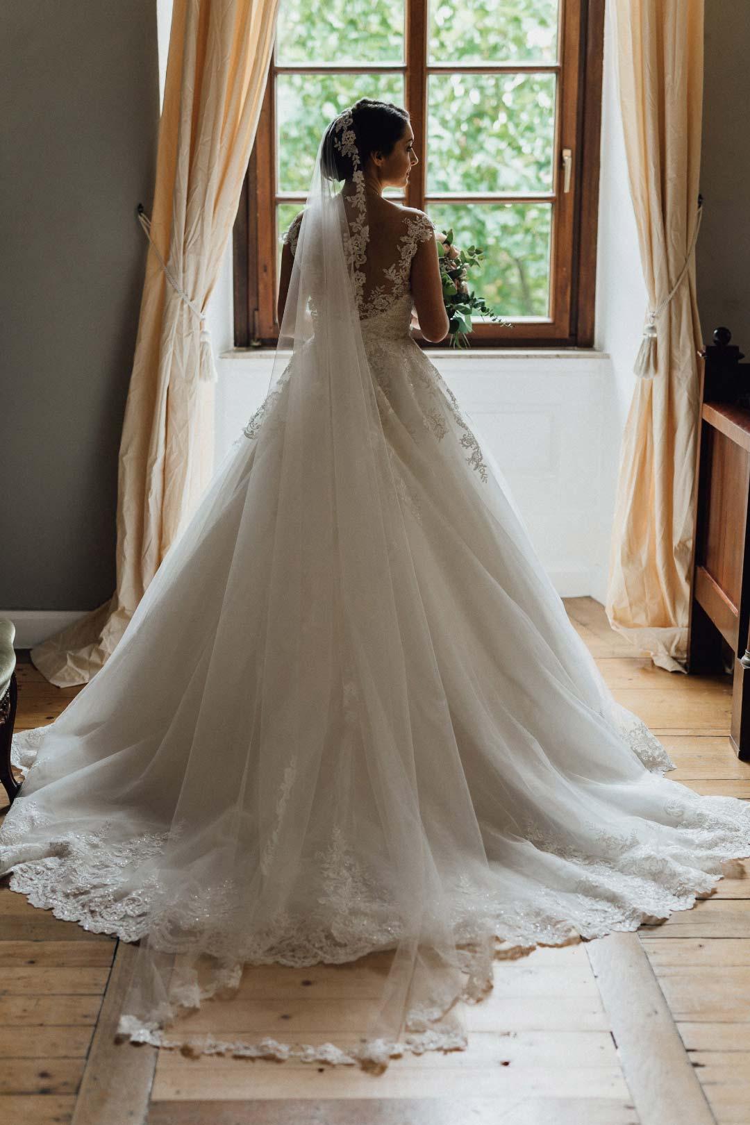 Das Brautkleid der Braut von hinten zusammen mit ihrem Schleier