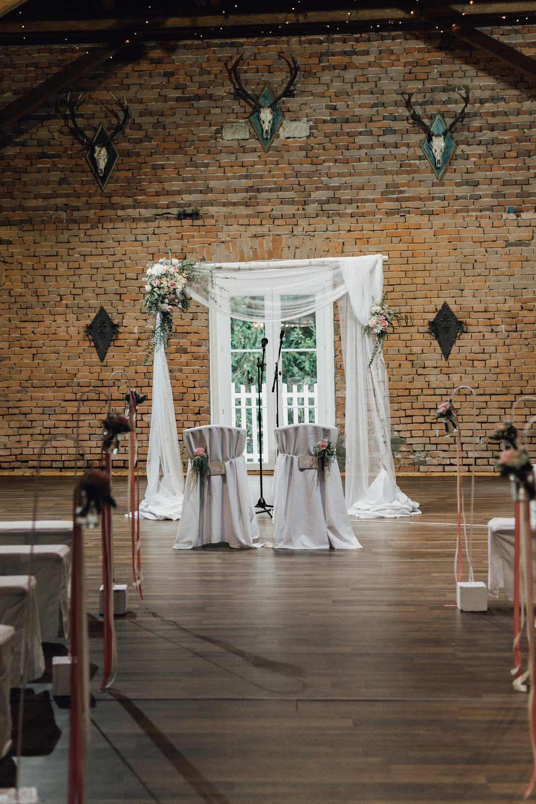 Ort der Trauung mit den Hochzeitsbogen und Stühlen davor