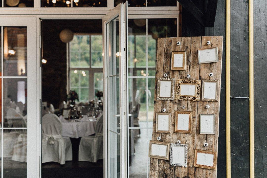 Sitzplan bei der Hochzeit mit einer Holzplatte auf welcher Bilderrahmen mit den Tischen montiert sind
