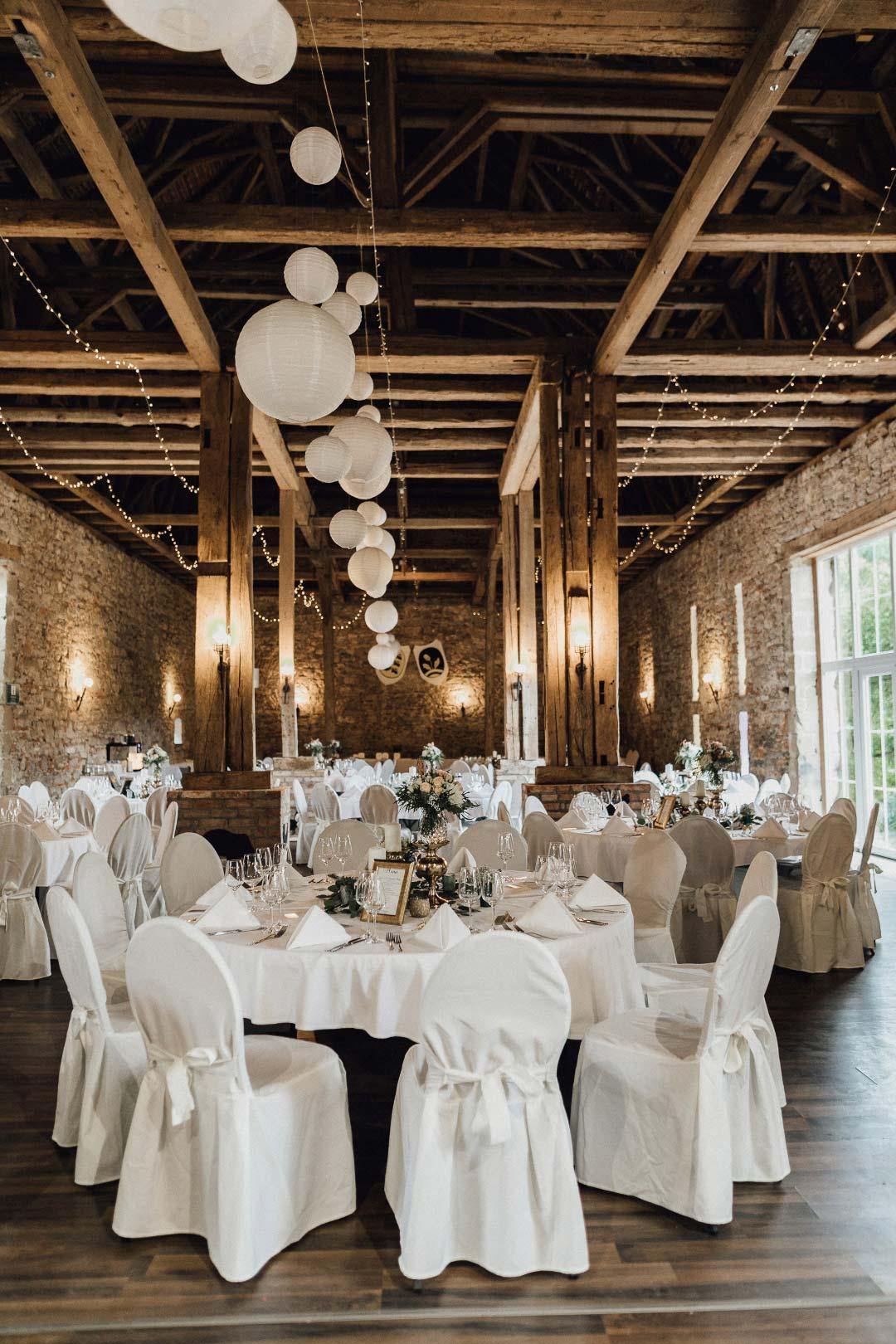 Alles vorbereitet für die Hochzeitsfeier mit in Hussen gehüllte Stühle und PomPoms an der Decke