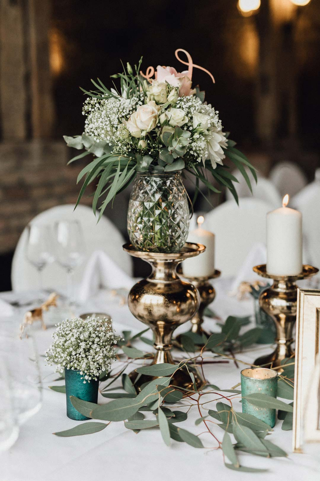 Tischdekoration am Tag der Hochzeit mit Schleierkraut und Gold Akzenten