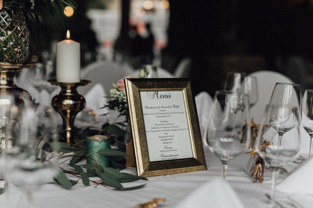 Menükarte bei der Hochzeit in einem goldenen Rahmen auf dem Tisch