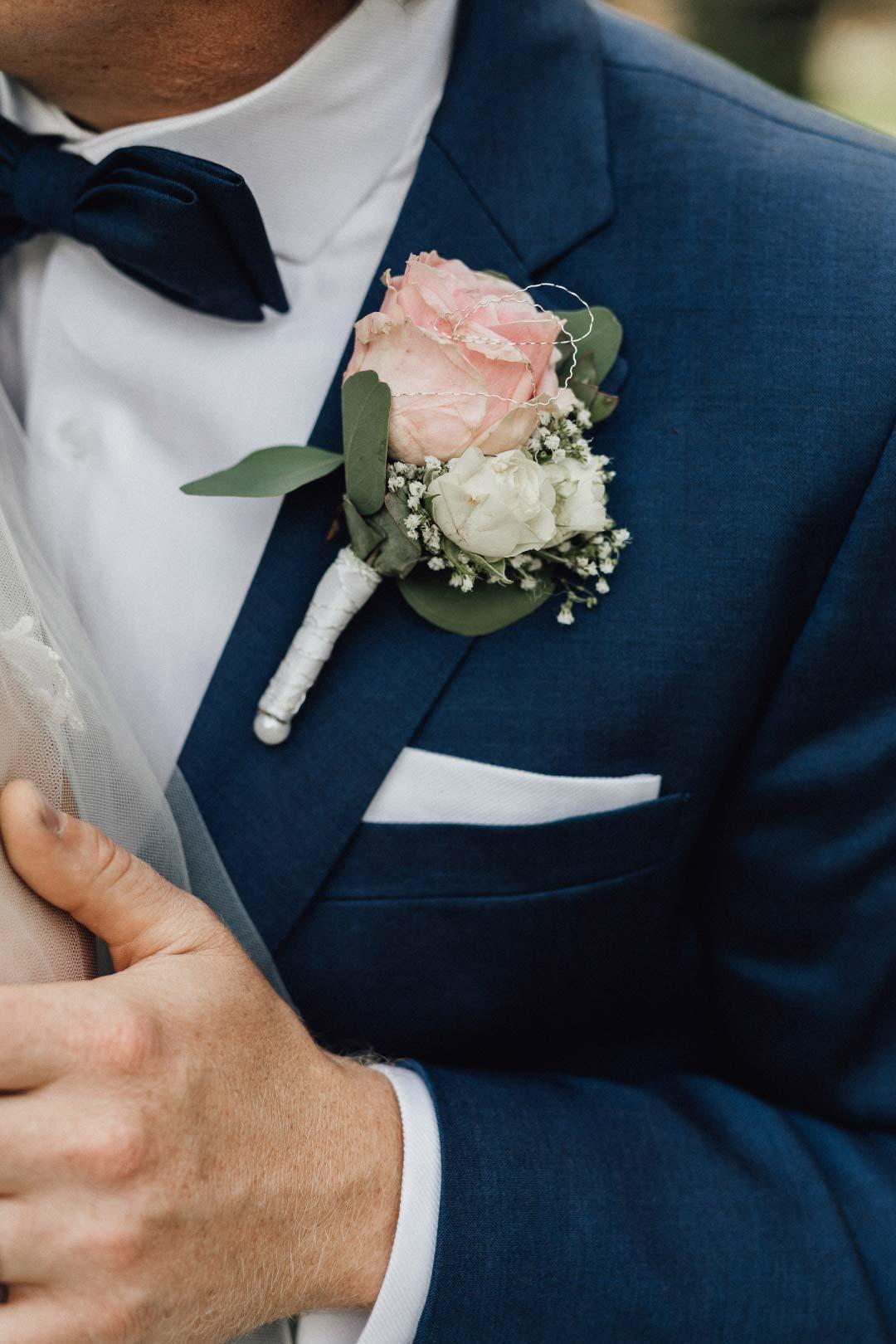 Ansteckblume für den Bräutigam mit einer großen Rose und etwas Schleierkraut