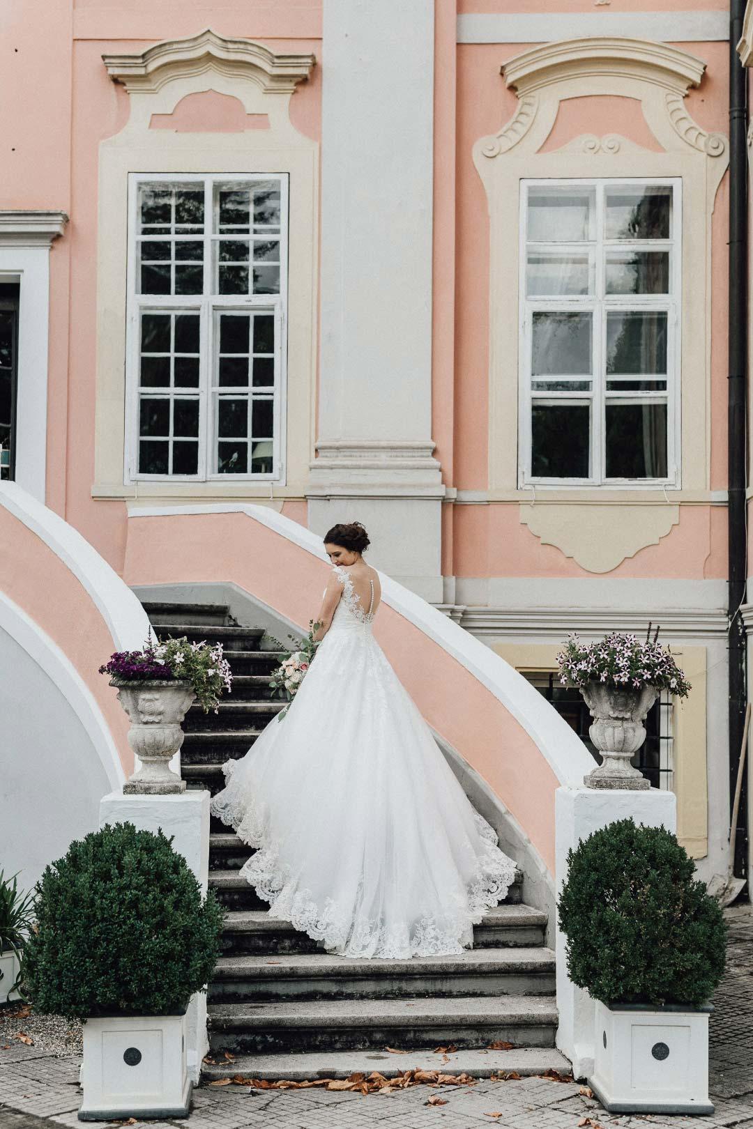 Foto der Braut auf einer Treppe an der Location der Hochzeitsfeier