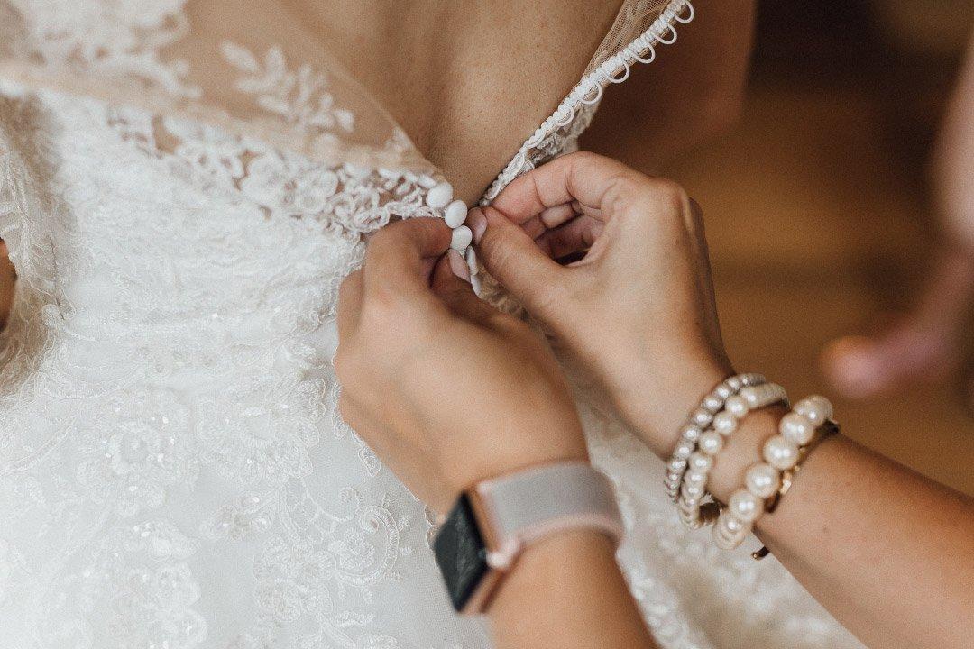 Das Brautkleid der Braut wird zugeknöpft