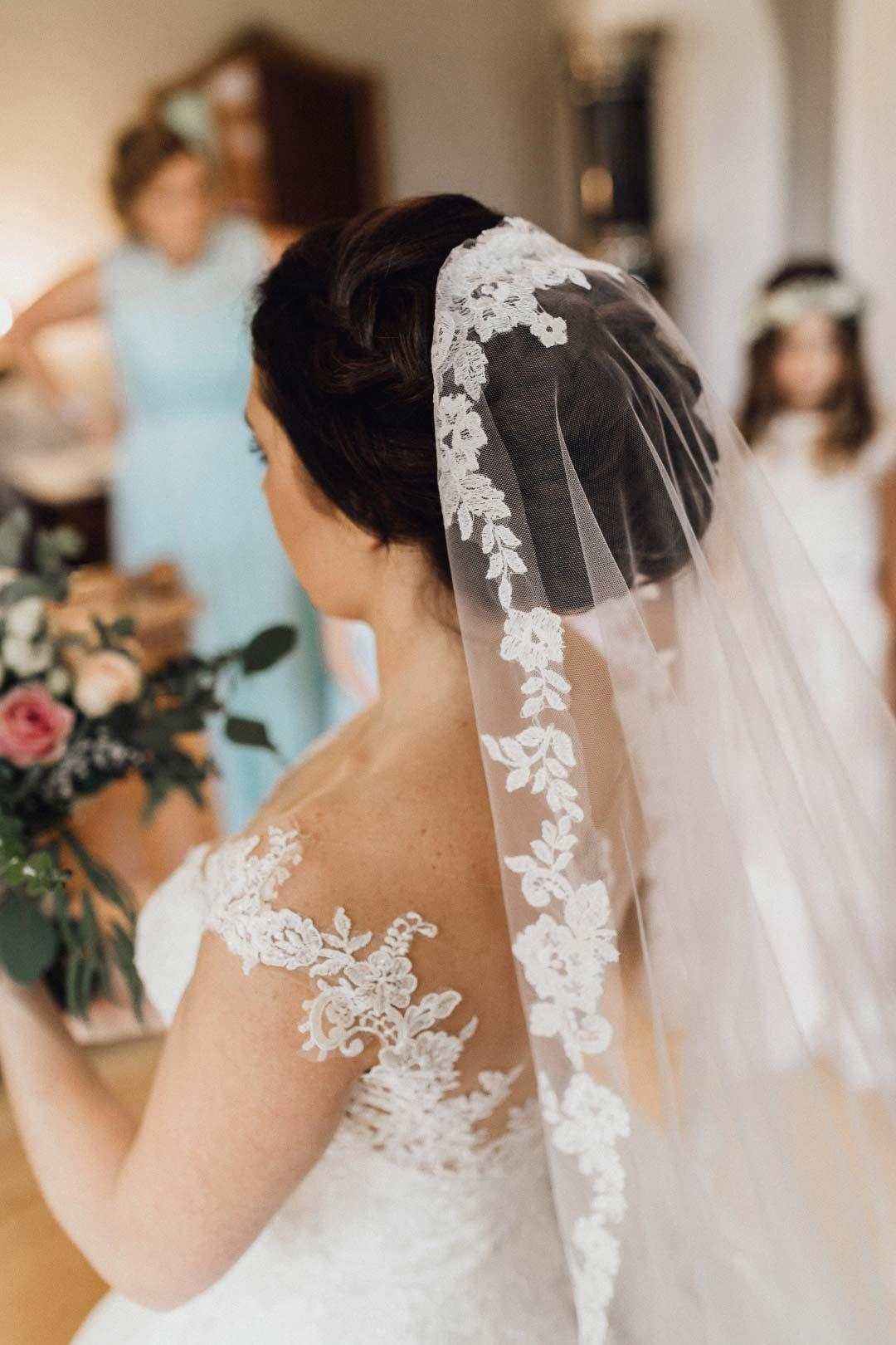 Die fertig gestylte Braut mit ihrem Schleier und Brautstrauß