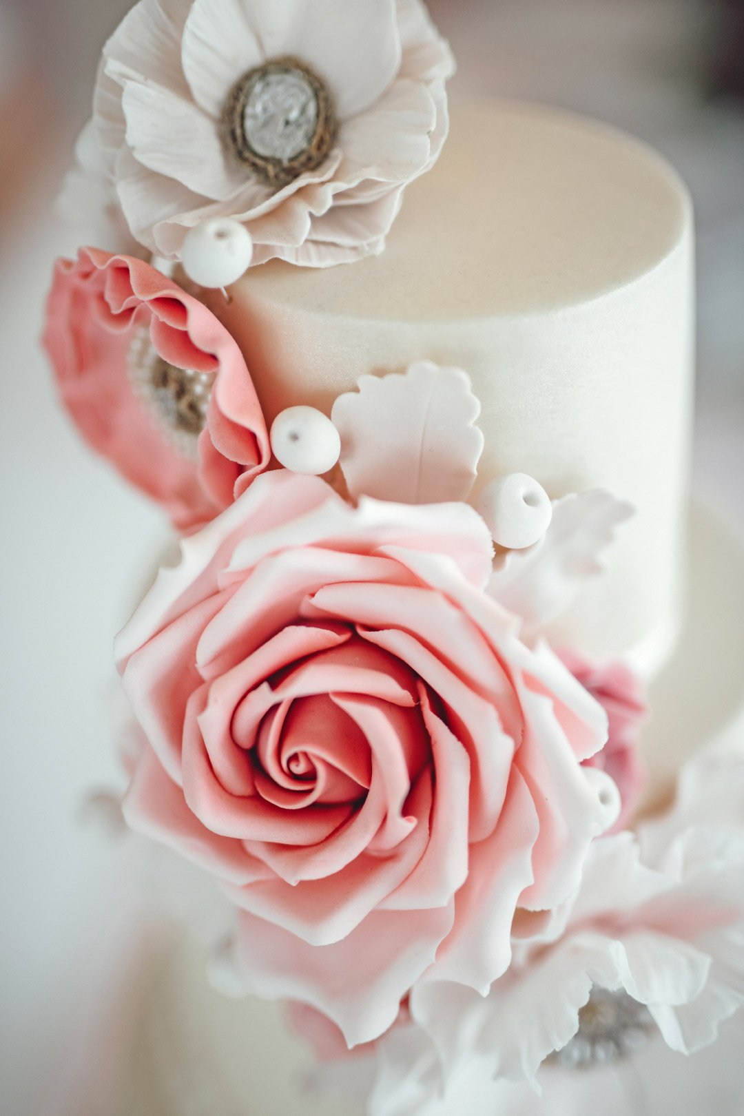 Aus Zuckerpaste modellierte Blumen an einer Hochzeitstorte