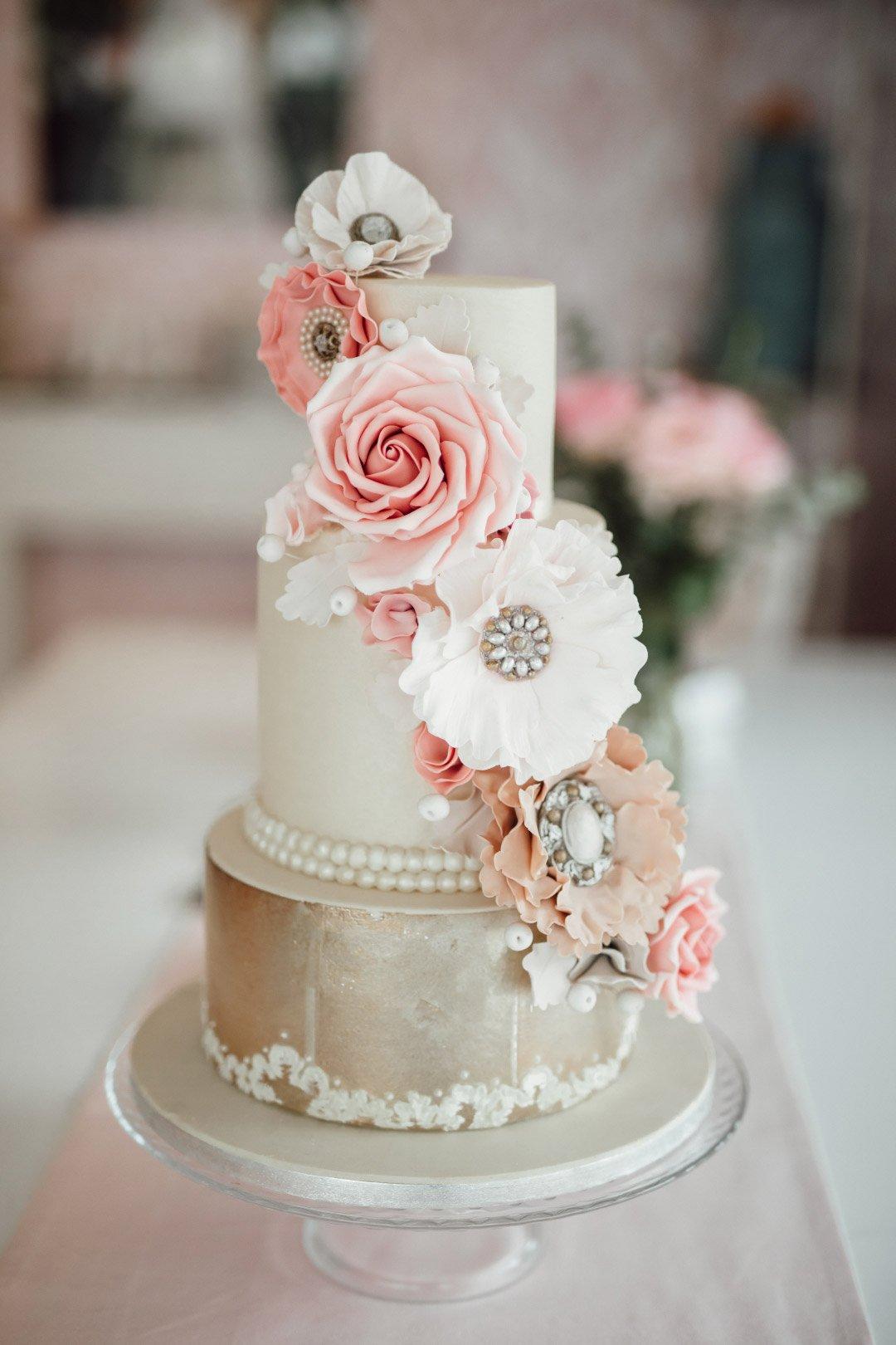 Dreistöckige Hochzeitstorte mit aus Zuckerpaste modellierten Blumen