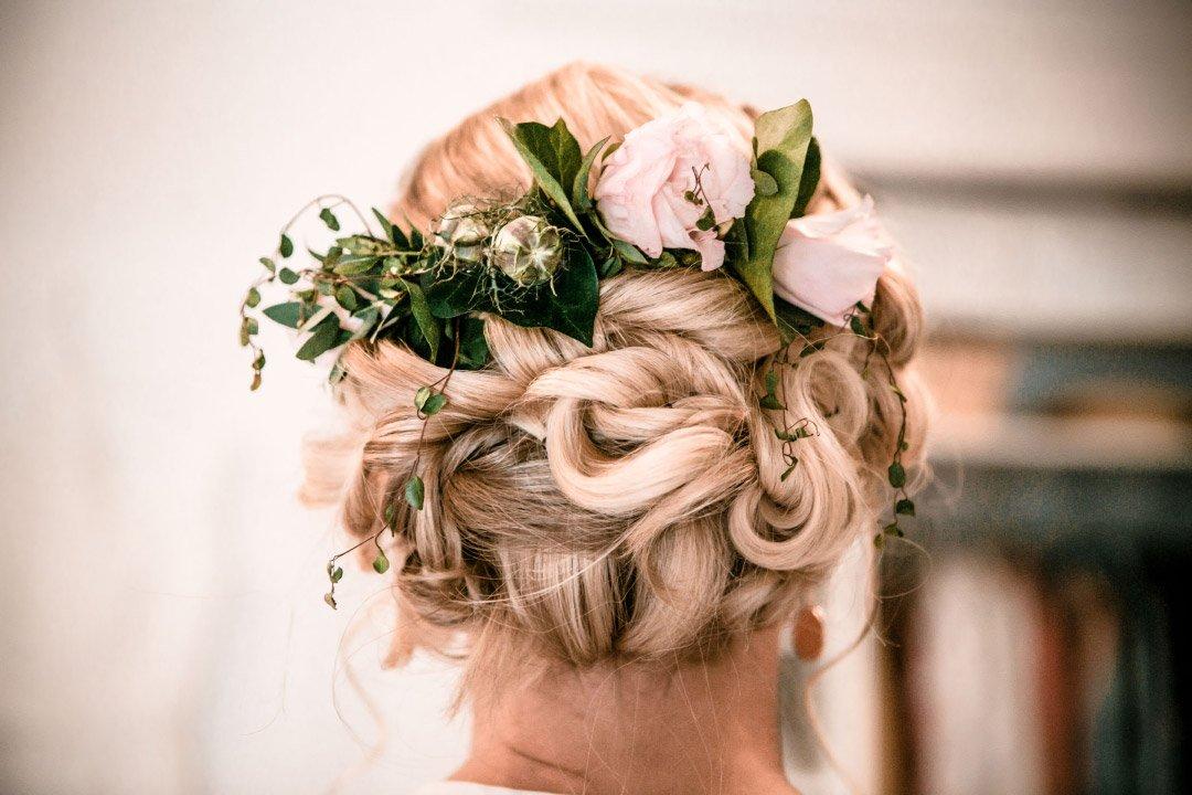 Hochsteckfrisur mit Blumen von der Braut am Tag der Hochzeit