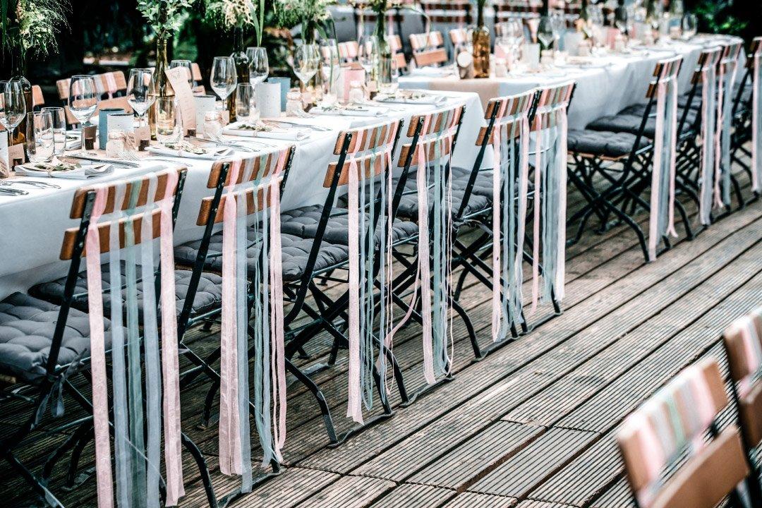 Holzstühle bei der Hochzeit mit Bänder verziert