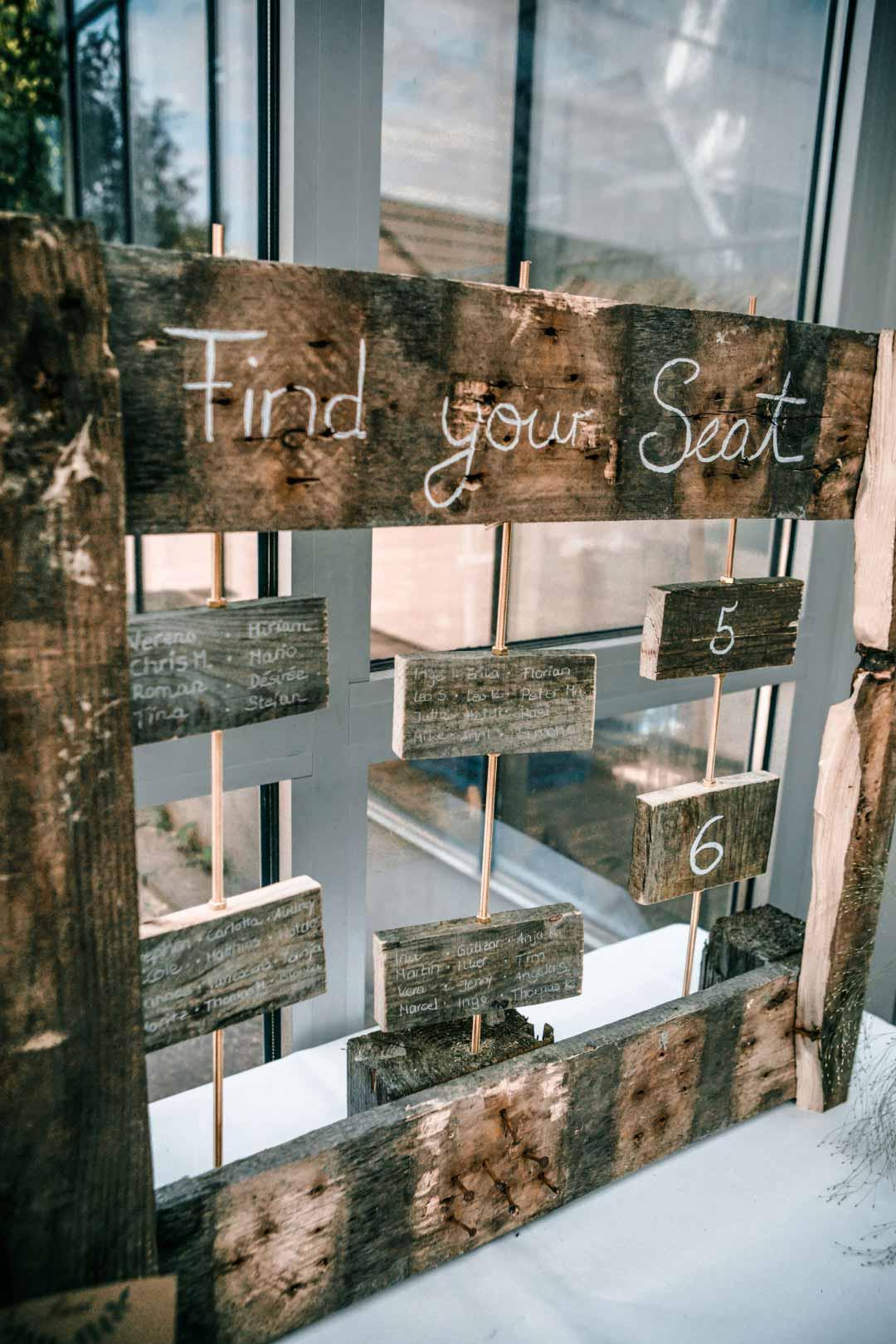 Rustikaler Sitzplan aus Holz bei der Hochzeit