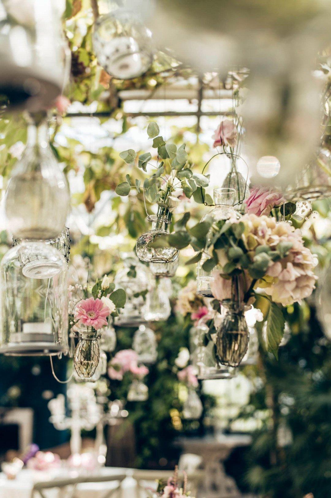 Blumen in kleinen Vasen von der Decke hängend als Dekoration bei der Hochzeit