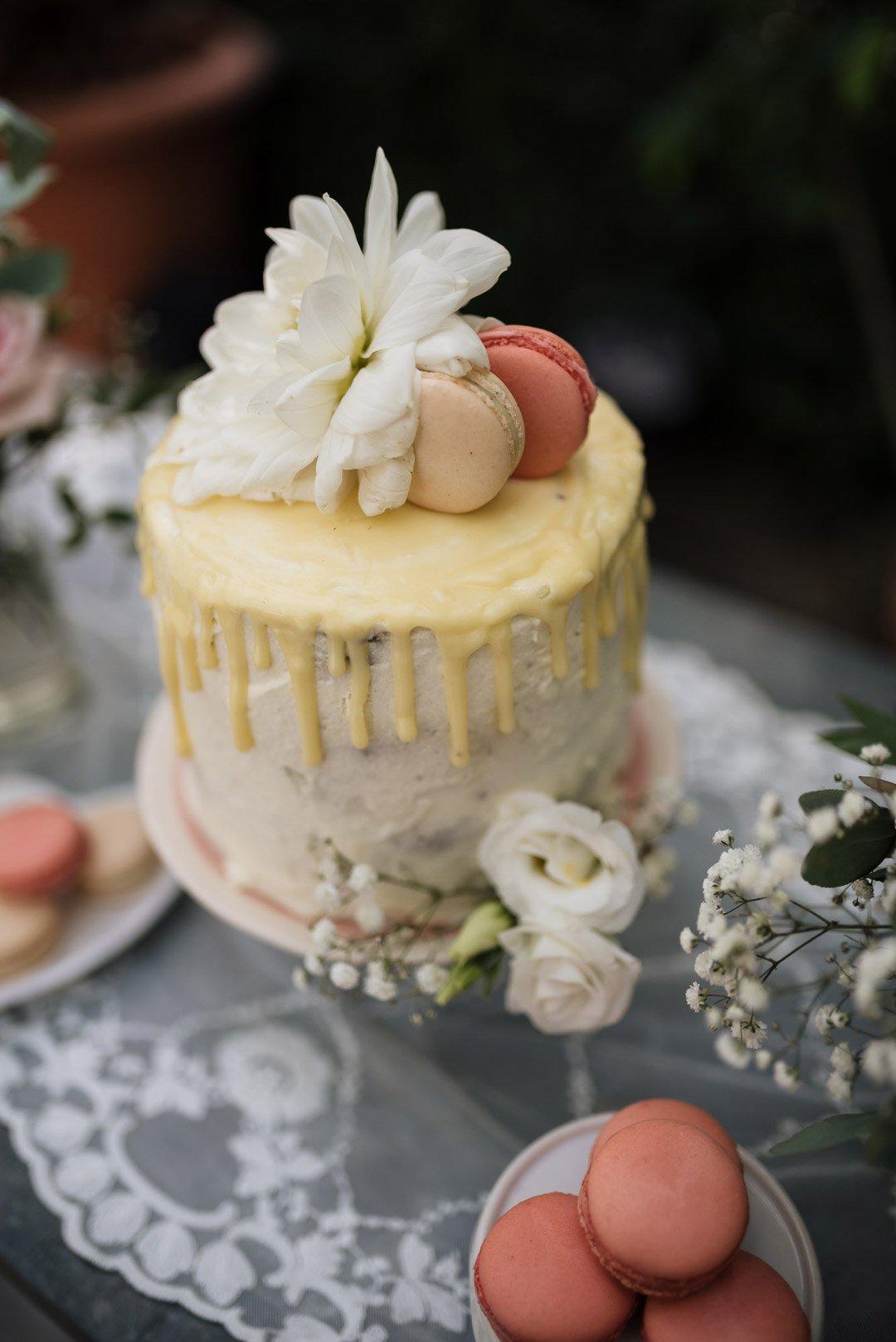 Drip Cake in Gelb und Weiß zusammen mit Macarons