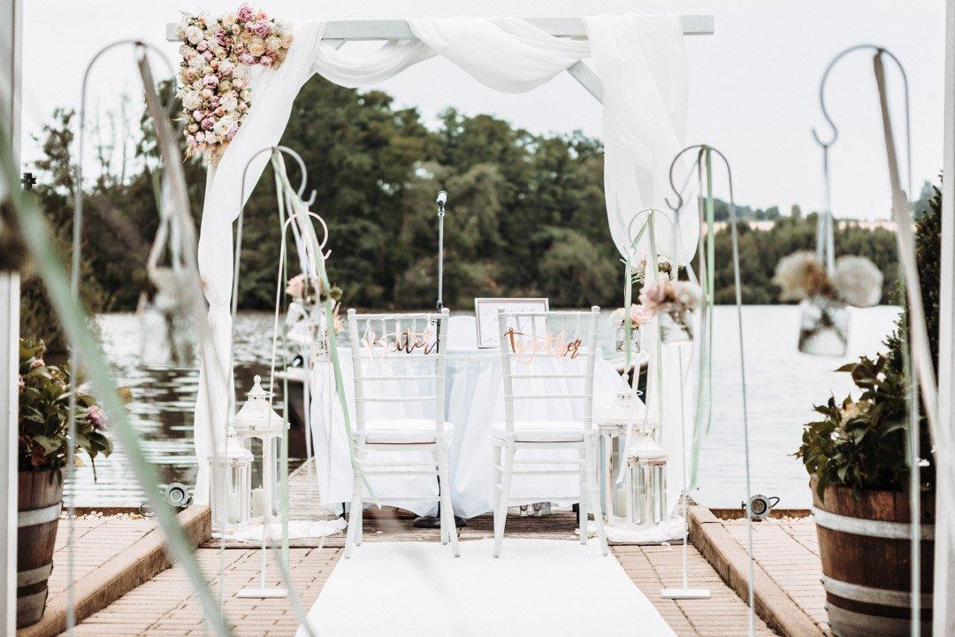 Hochzeit direkt am Wasser mit einem Traubogen in Weiß