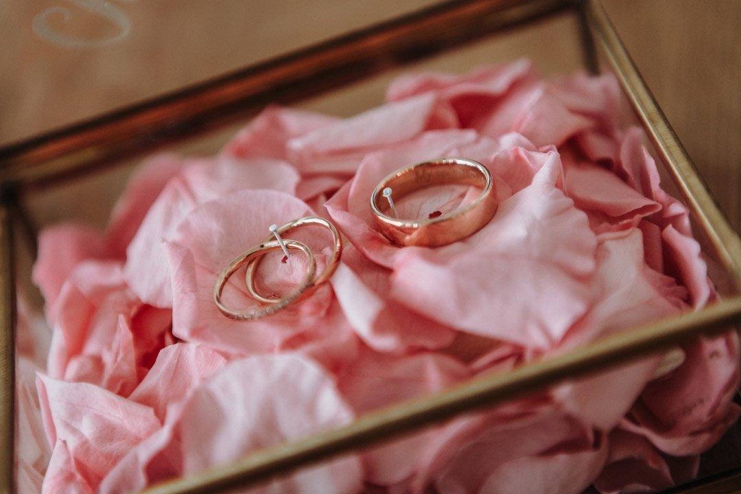 Die Trauringe in einer Glasschachtel aus Rosenblätter gebettet