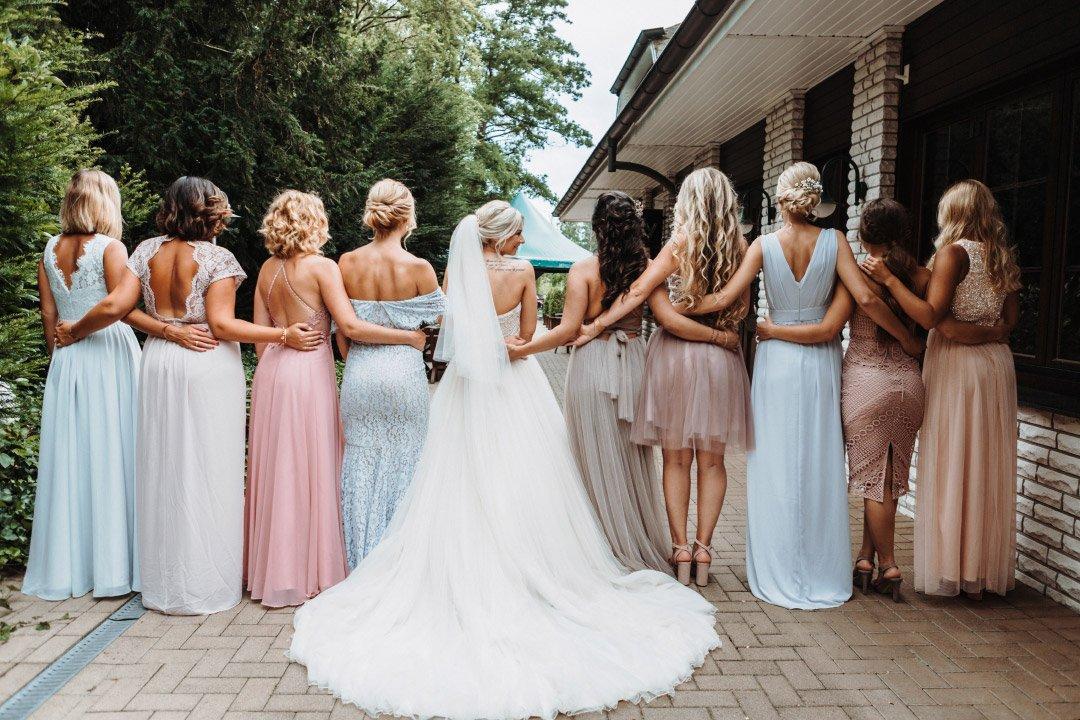 Braut zusammen mit ihrer Trauzeugin und Brautjungfern in Kleidern in Blush, Rose und Pastell