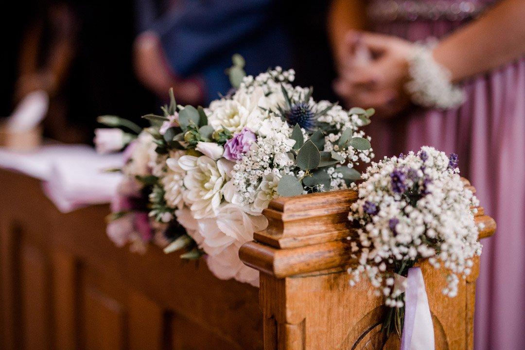 Blumen als Dekoration an der Kirchenbank