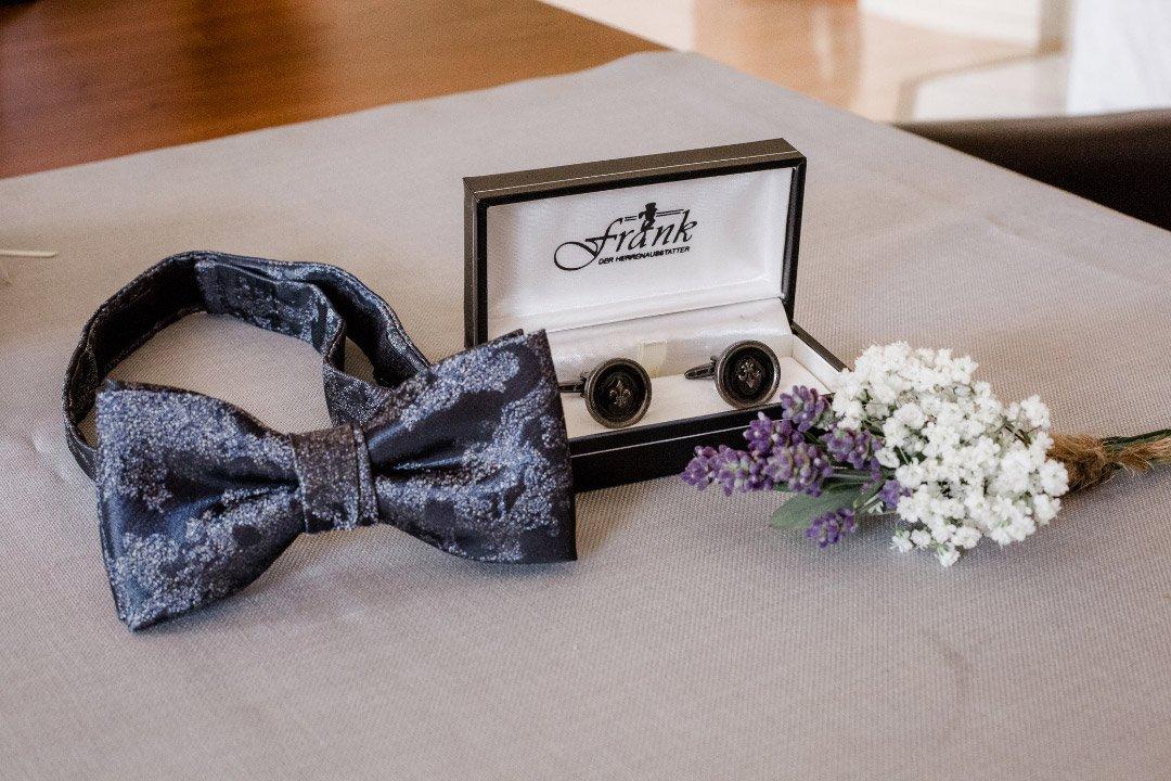 Fliege und Manschettenknöpfe vom Bräutigam am Tag der Hochzeit