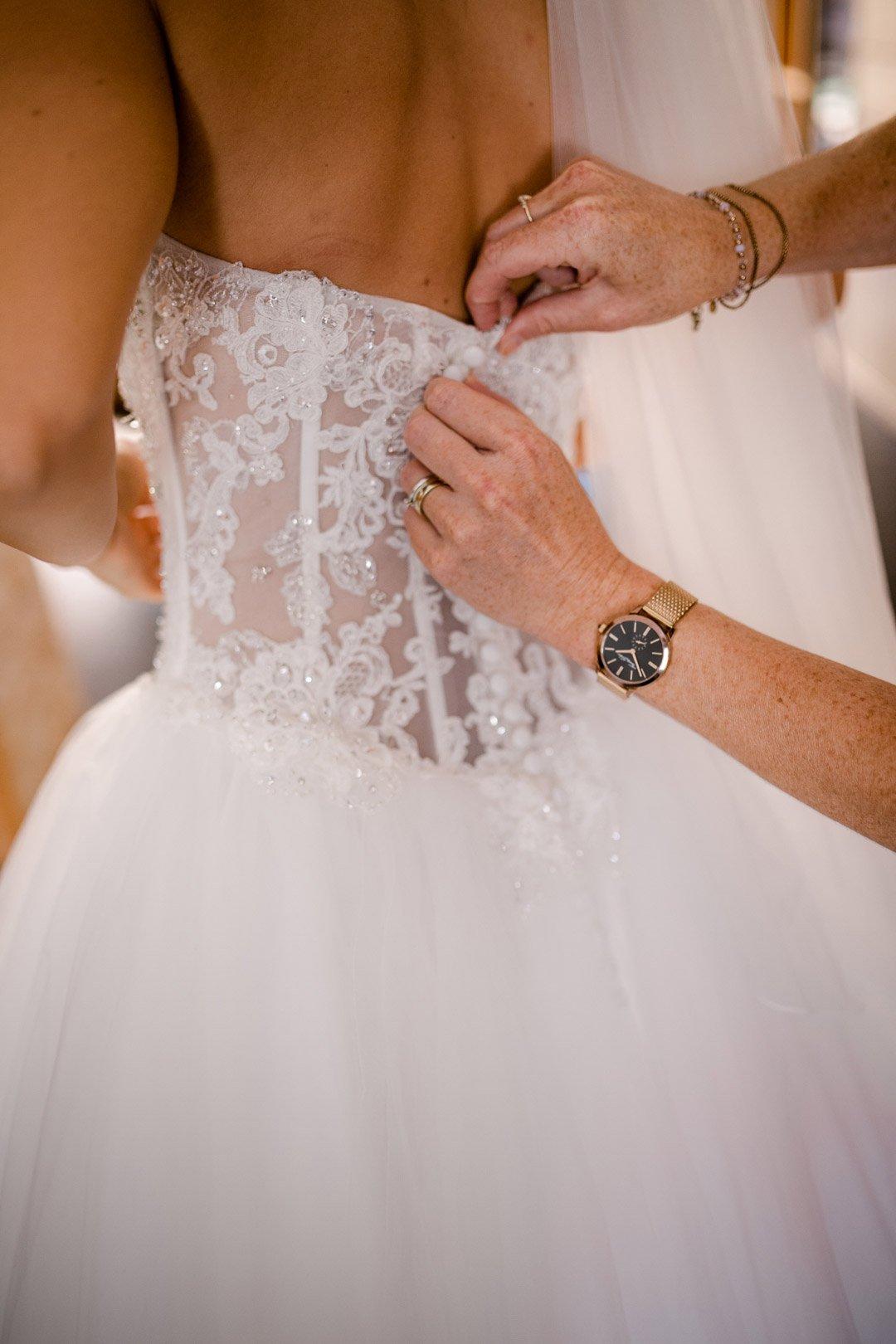 Die Knöpfe am Brautkleid werden beim Getting Ready zugeknöpft