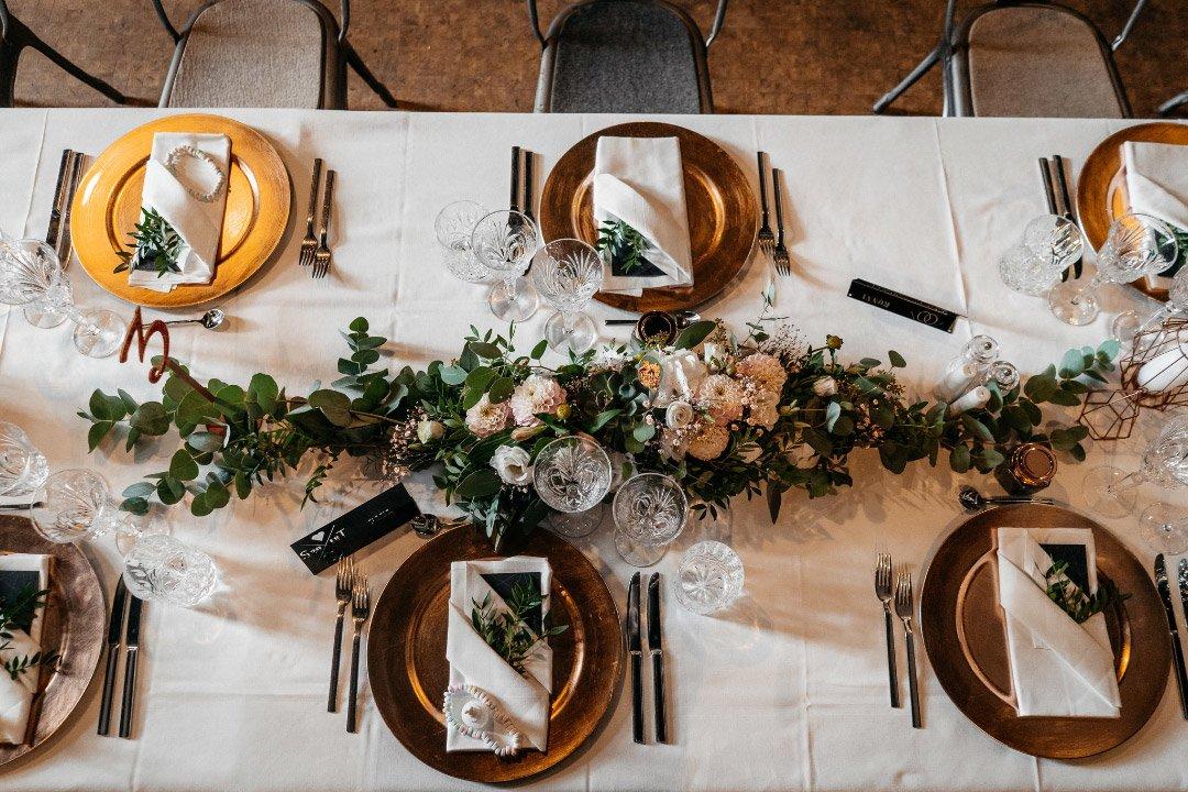 Tischdekoration bei einer langen Tafel auf der Hochzeit im Kesselhaus von Alte Spinnerei Kolbermoor