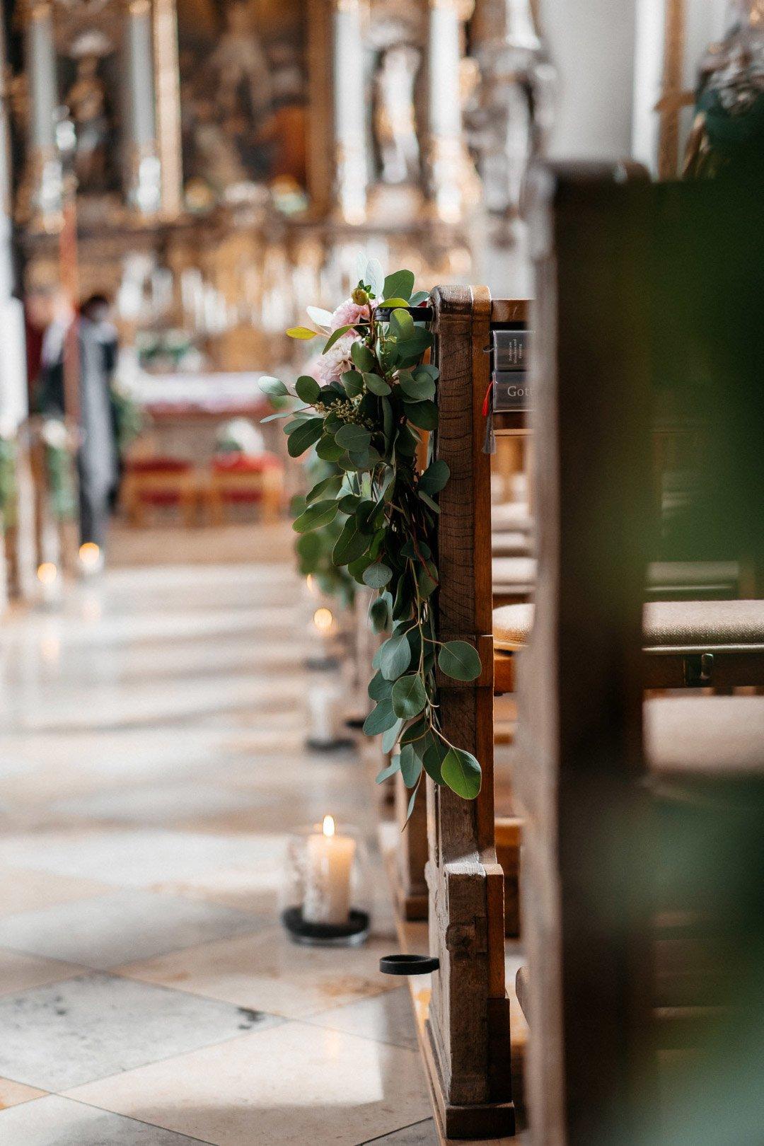 Blumendekoration an der Kirchenbank in der Kirche für die Hochzeit