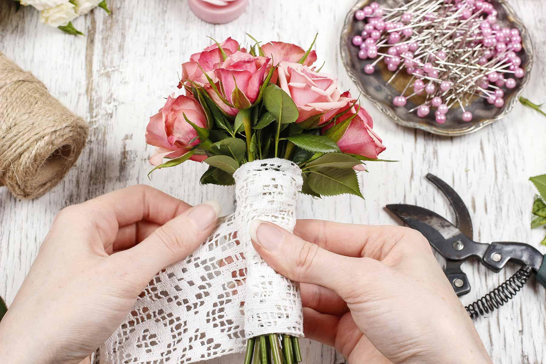 Blumen bei der Hochzeit mit Spitzenband umwickelt