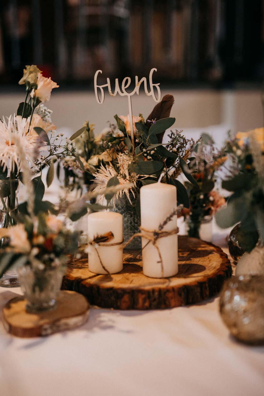 Tischdeko mit Baumscheibe bei der Boho-Hochzeit auf dem Bauernhof