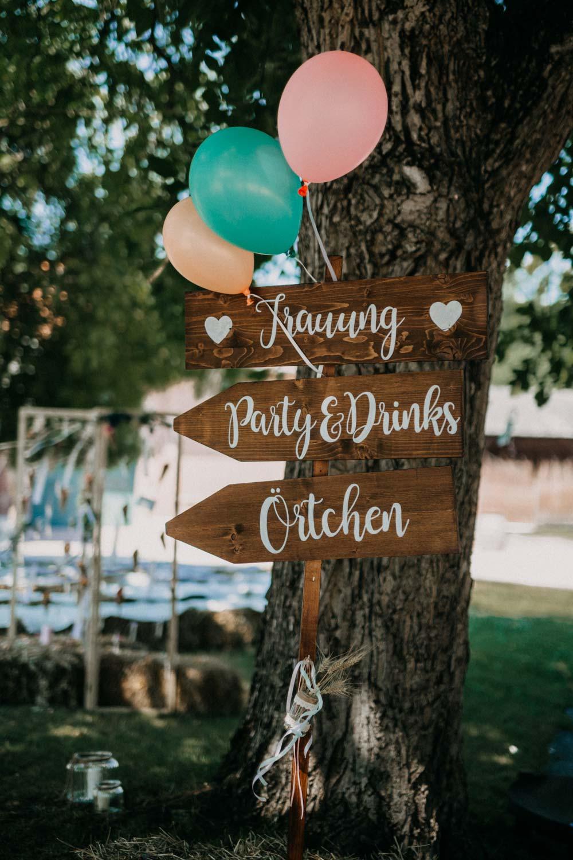 Holzschild als Wegweiser bei der Boho-Hochzeit auf dem Bauernhof