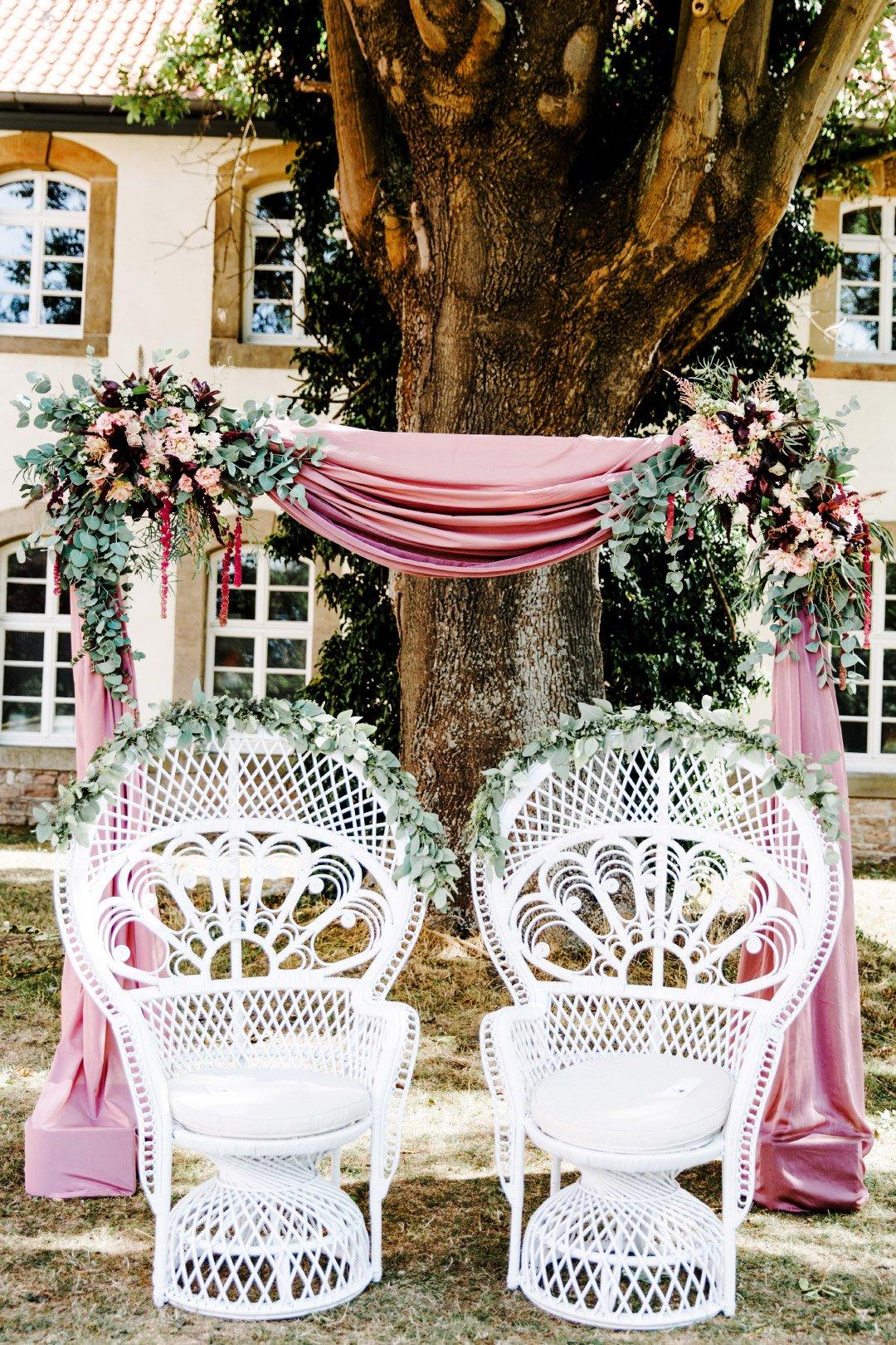 Stühle für das Brautpaar am Traubogen