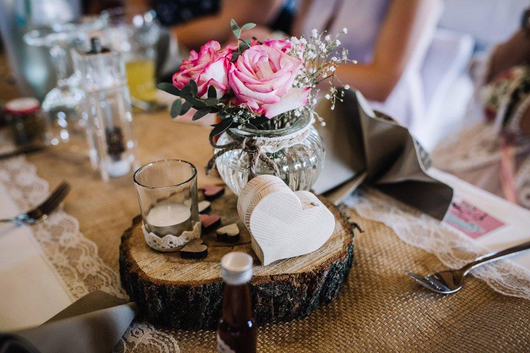 Ländliche Sommer-Hochzeit im rustikalen Stil: Tischdeko mit Holzscheibe
