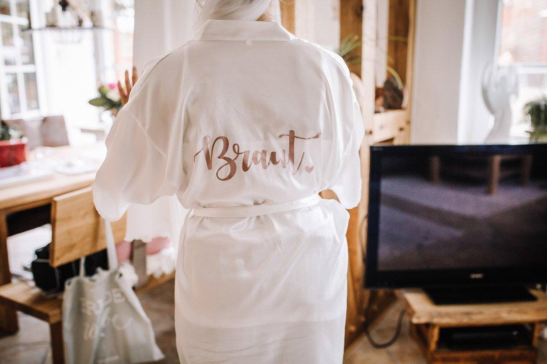 Braut im Morgenmantel mit Braut Aufschrift