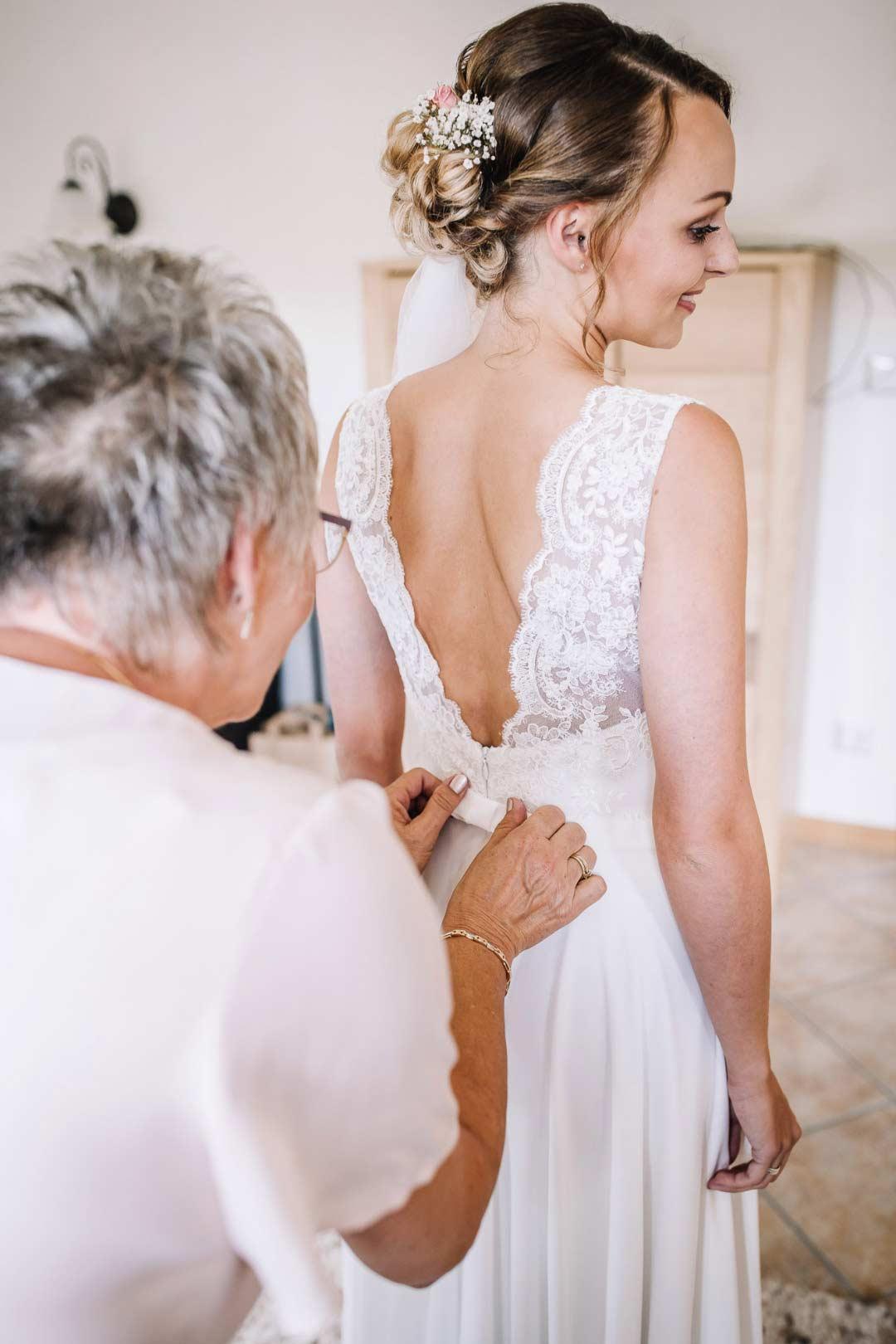 Braut bekommt Brautkleid zugeknöpft