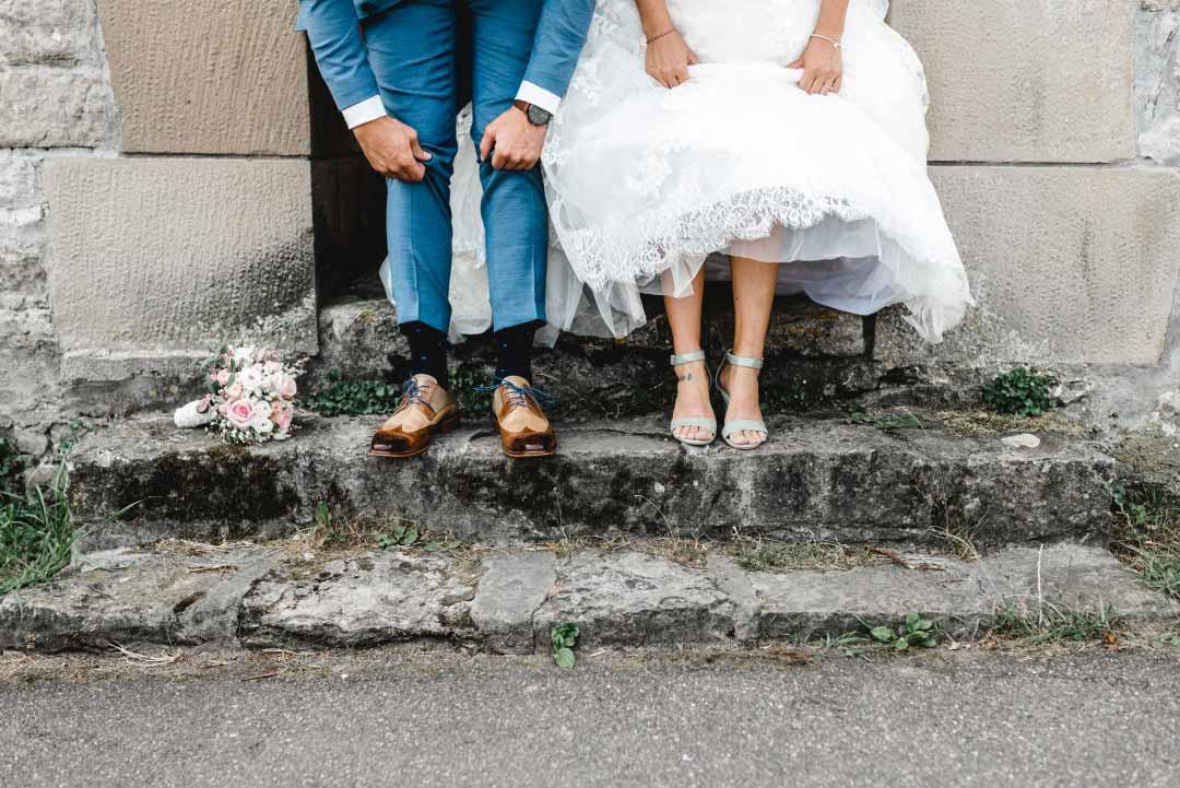 Braut und Bräutigam zeigen ihre Schuhe
