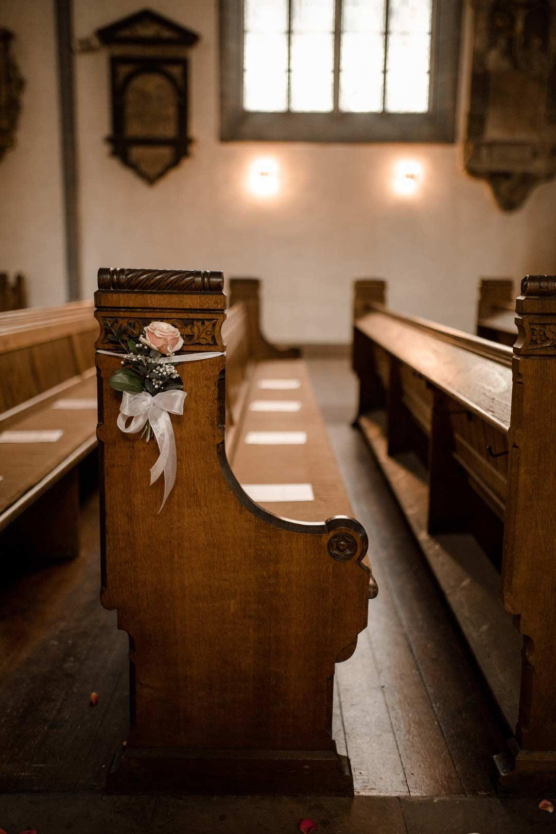Kirchenbank mit Blumenschmuck und Kirchenhefte