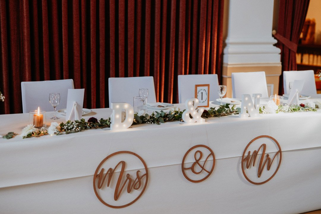 Dekoration von dem Brautpaar Tisch mit Holzanhängern und Leuchtbuchstaben