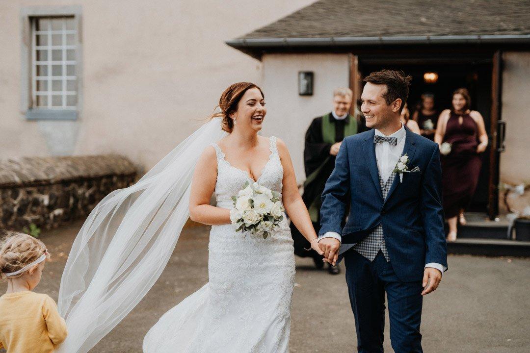Braut und Bräutigam bei der Hochzeit in Roségold, weiß und viel Greenery