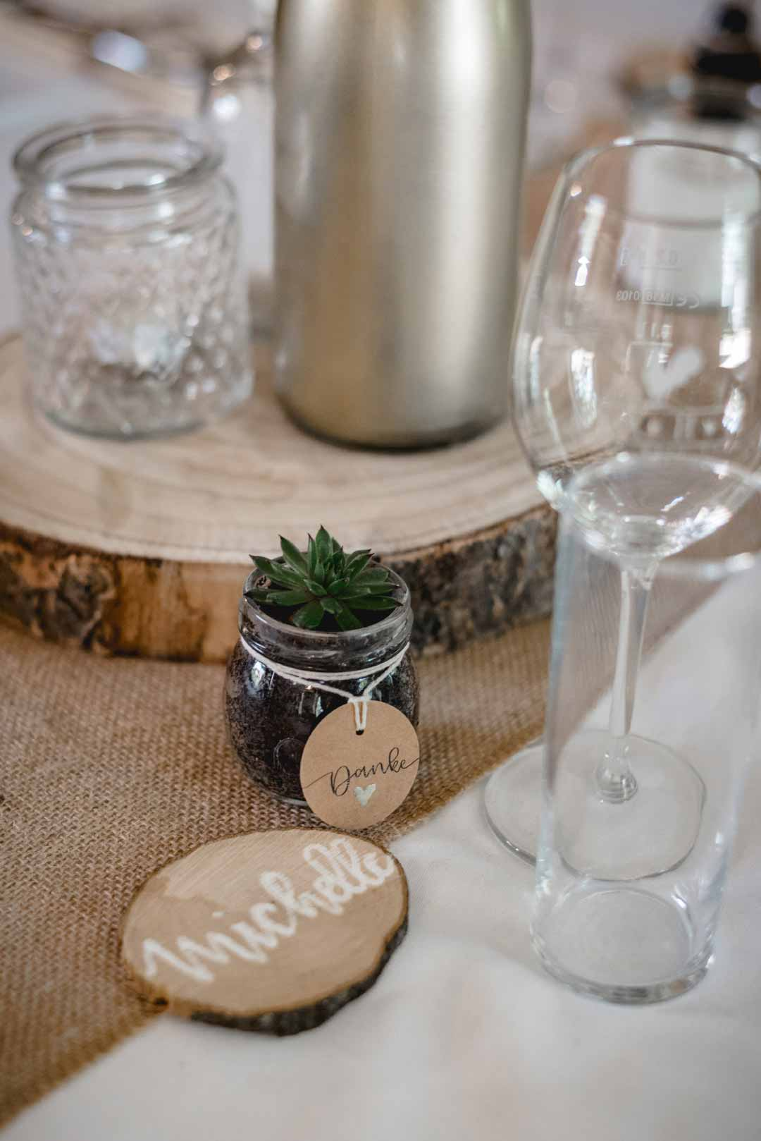Kleine Pflanze im Glas als Gastgeschenk